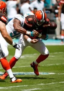 Cleveland Browns quarterback Cody Kessler (6) funnels the ball after he was sacked by Miami Dolphins defensive end Cameron Wake (91) during an NFL football game, Sunday, Sept. 25, 2016, in Miami Gardens, Fla. (AP Photo/Wilfredo Lee)